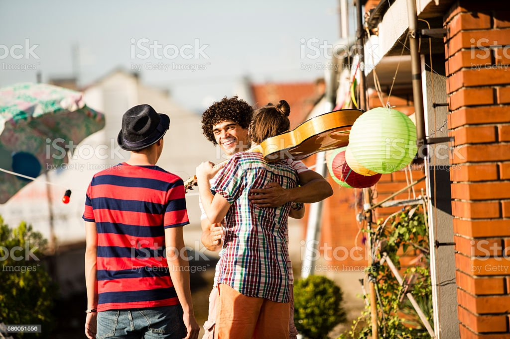 Welcoming  friends for rooftop party stock photo