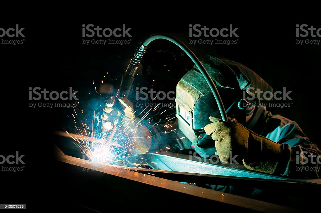 welder at work on metal structures stock photo