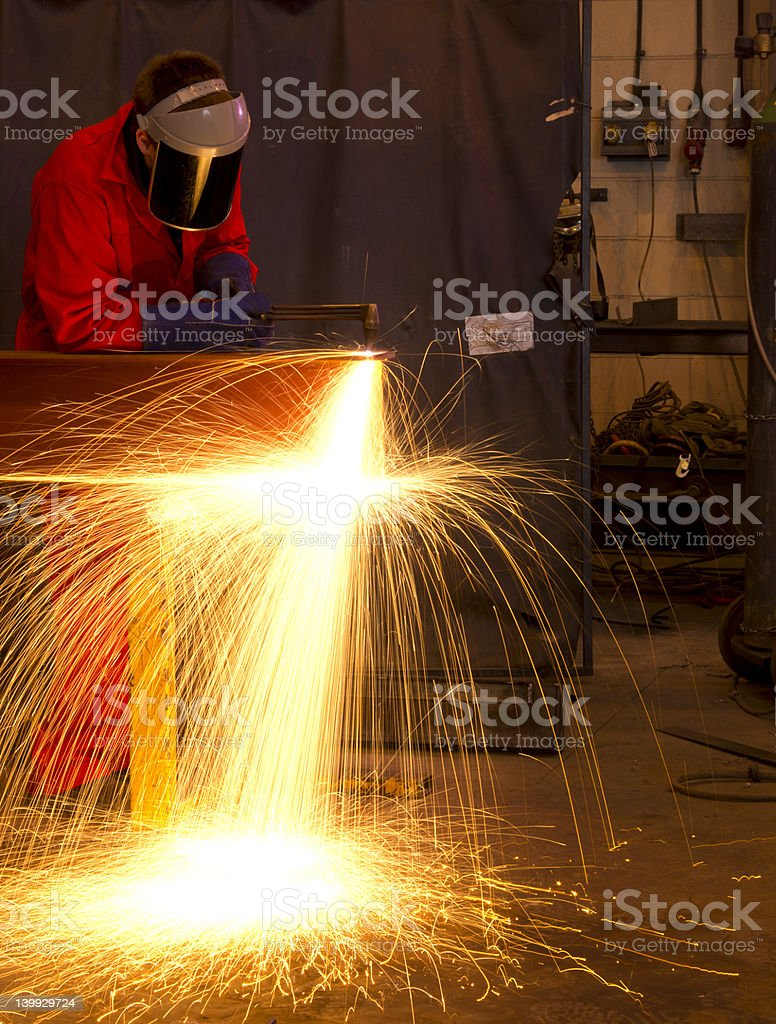 Welder in workshop manufacturing metal construction by cutting to...