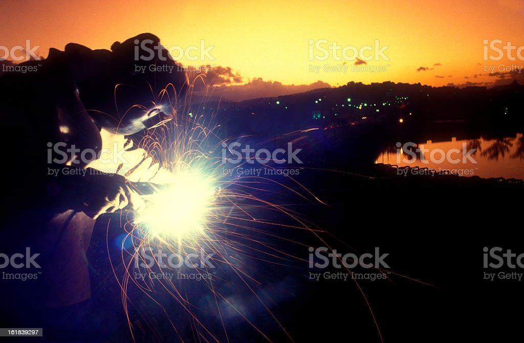 Welder creates sparks against sky after sunset royalty-free stock photo