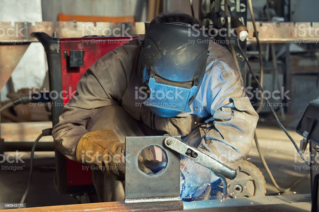 welder fabricates steel structures using semi-automatic welding stock photo