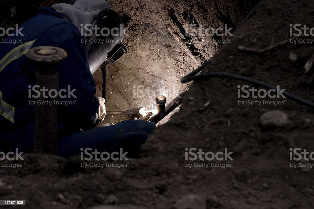Welder in a hole. stock photo