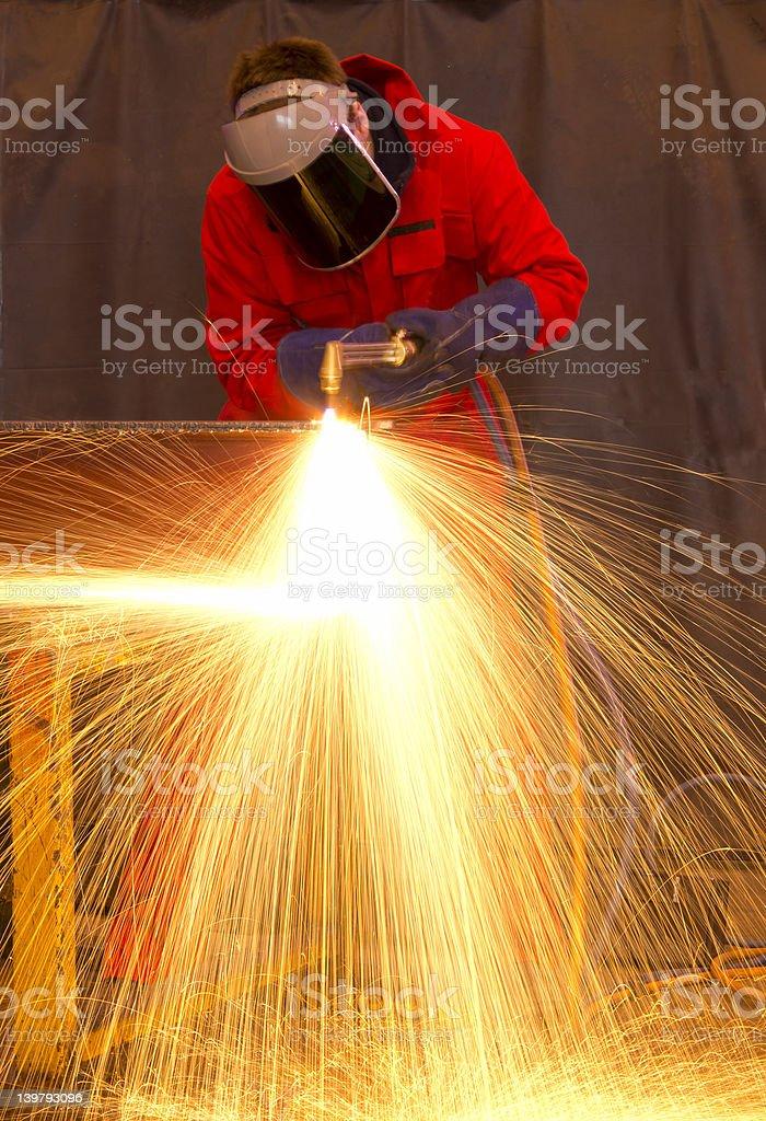 Welder in red creates huge  orange sparks stock photo