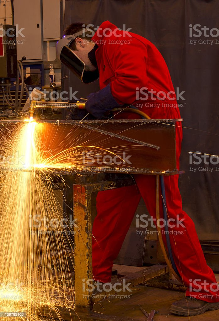 Welder in red overalls cuts metal. royalty-free stock photo