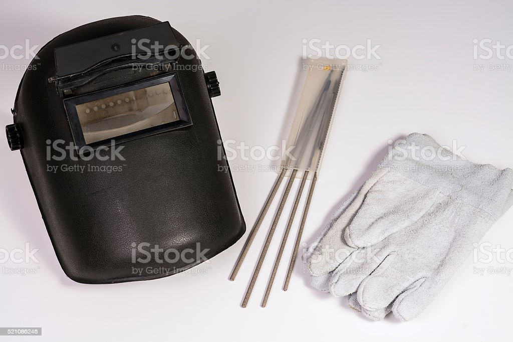 Welder mask near some electrodes and a pair of gloves. stock photo