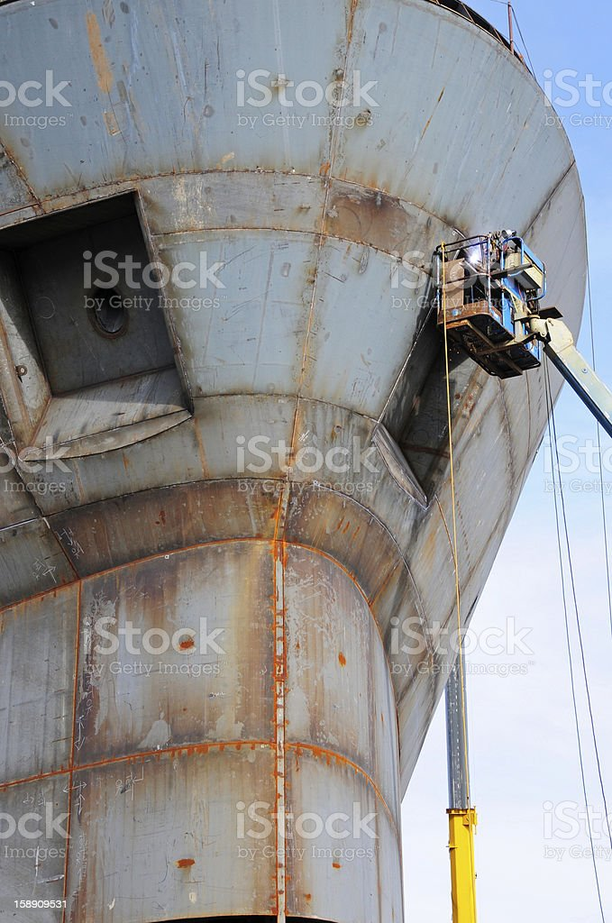 Welder on cherry picker in shipyard royalty-free stock photo