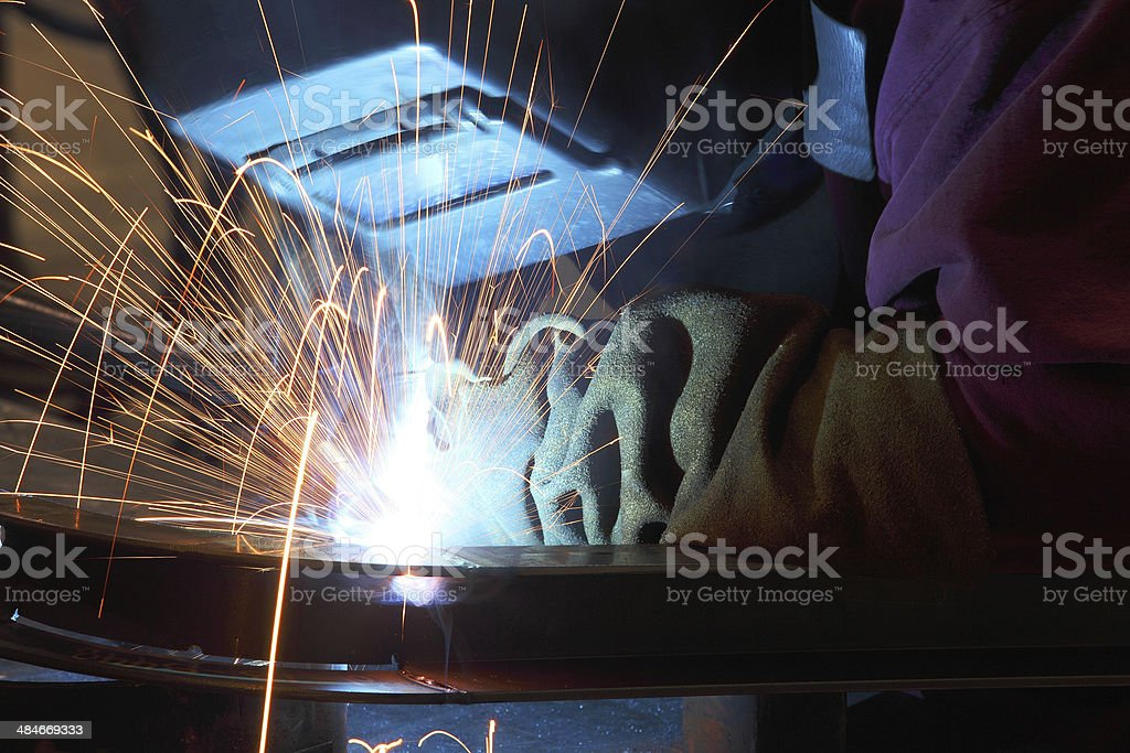 Sparks fly as an industrial welder welds two pieces of metal together.