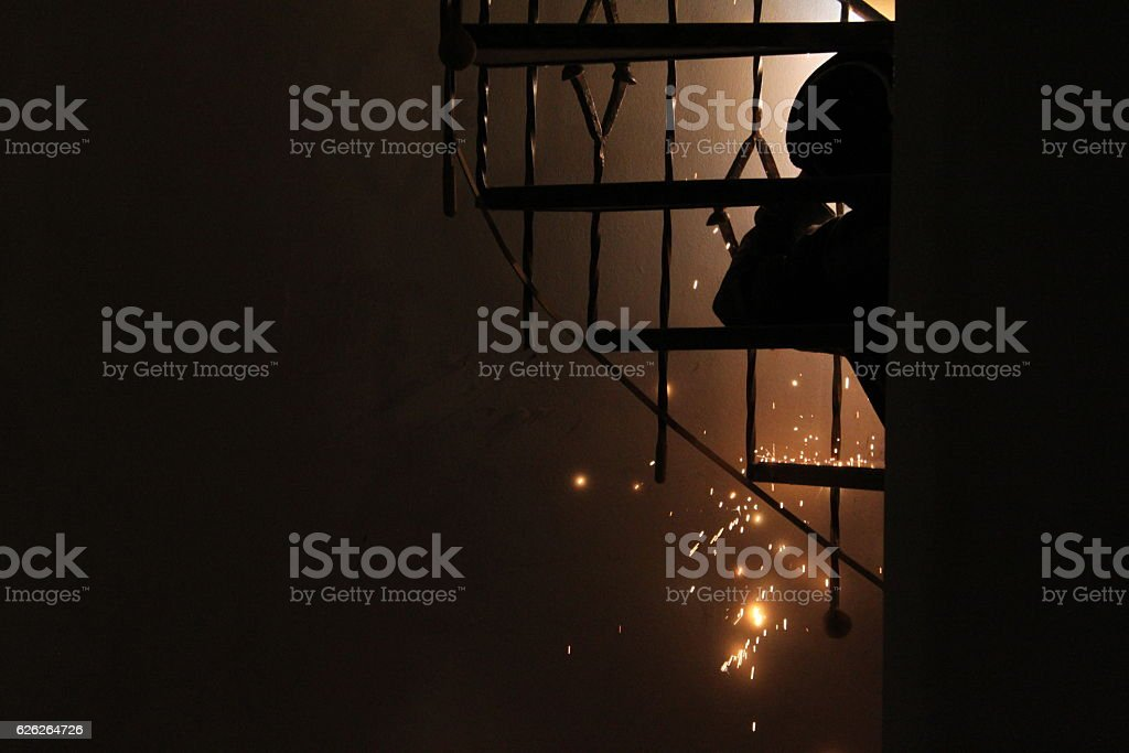 Welder produces sparks as he repairs an iron spiral staircase. stock photo