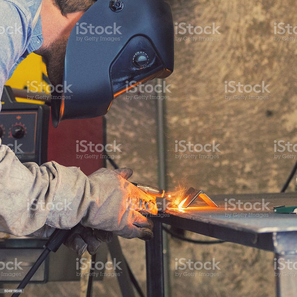 Welder using torch to weld pieces of metal in workshop stock photo