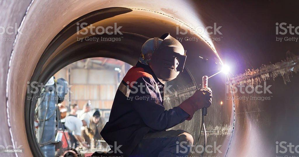 welder weld root weld from inside of big pipe stock photo