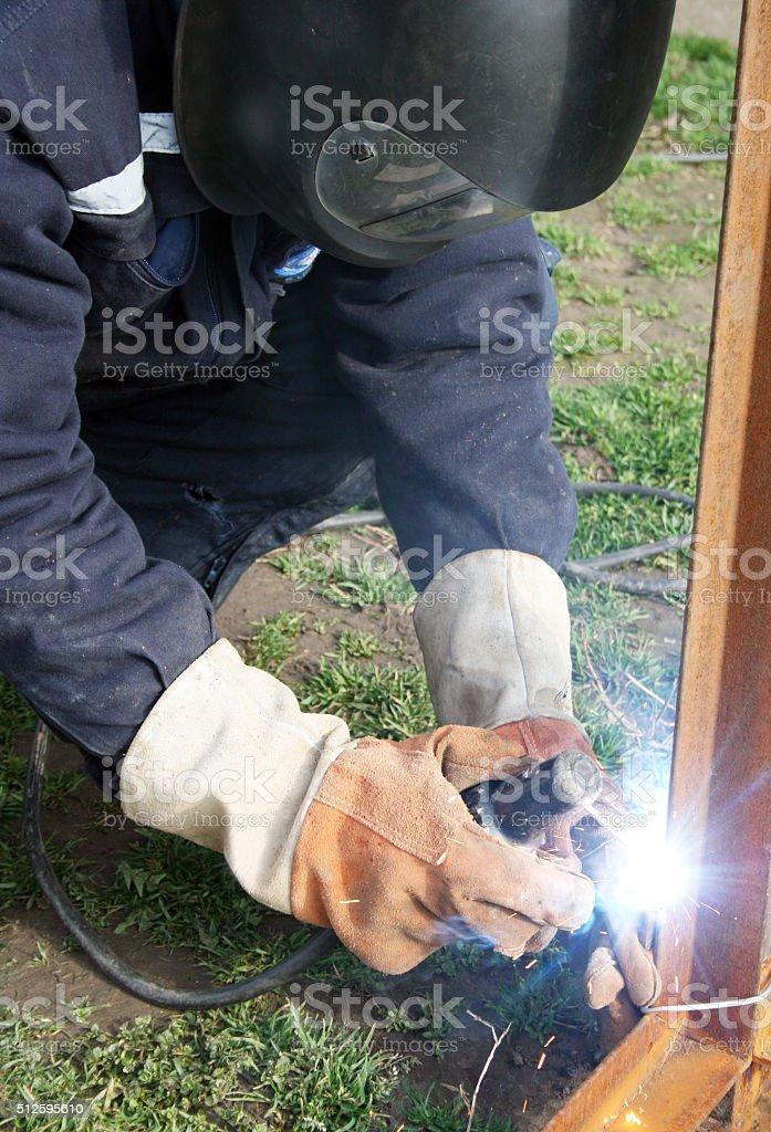 Welder welding a metal part stock photo
