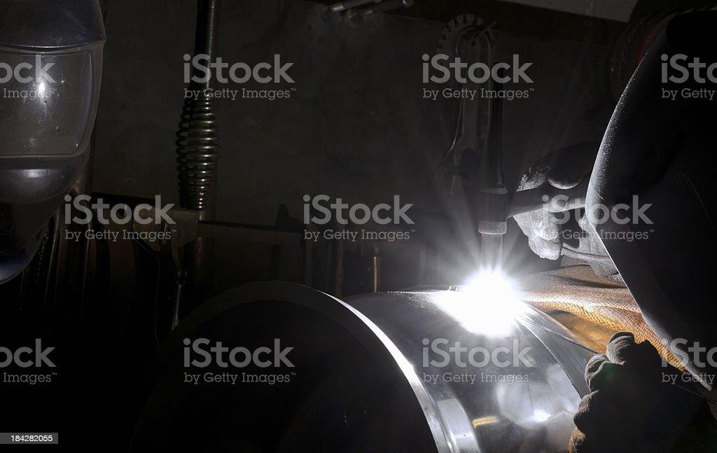 Welder welding aluminum with a TIG machine stock photo