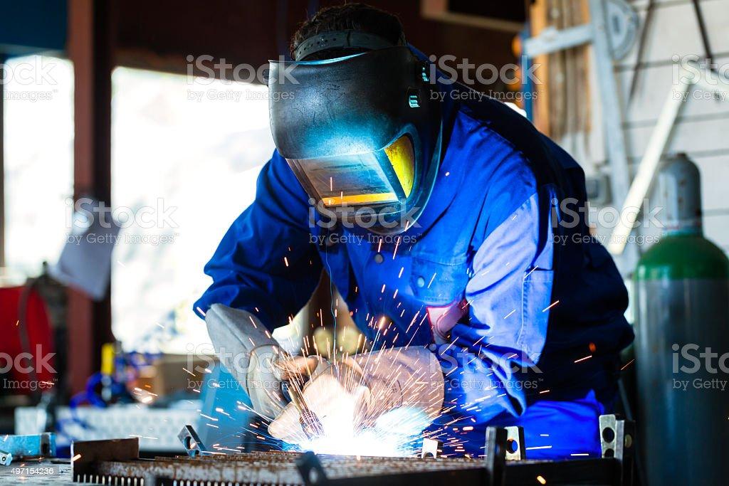 Welder welding metal in workshop with sparks stock photo