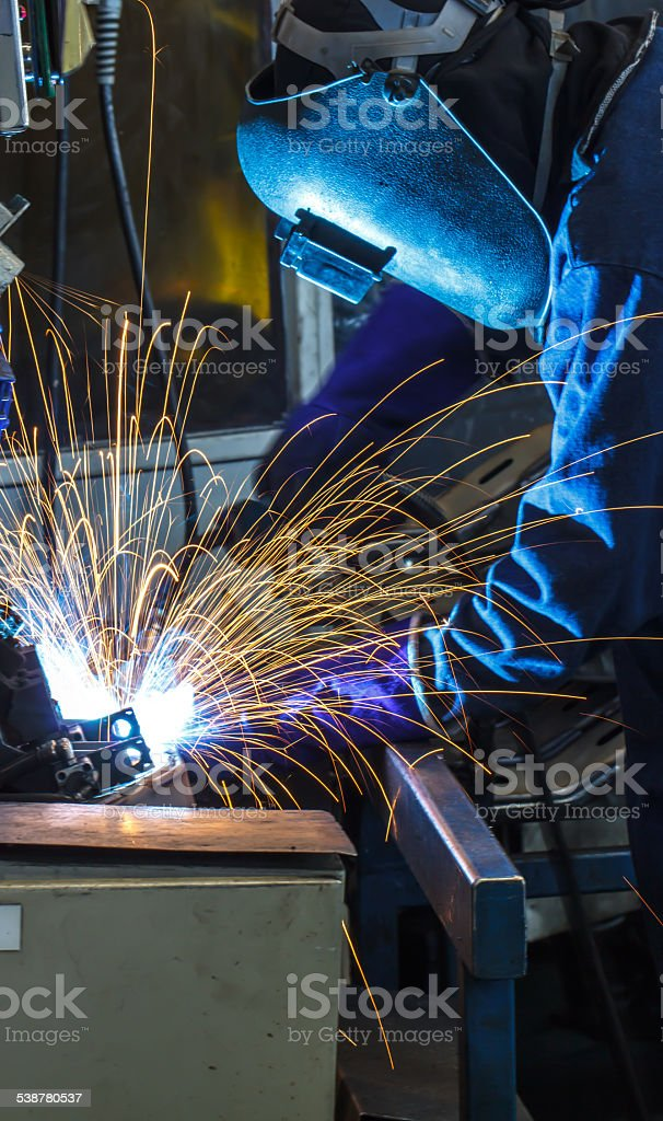 welder with protective mask welding metal and sparks stock photo