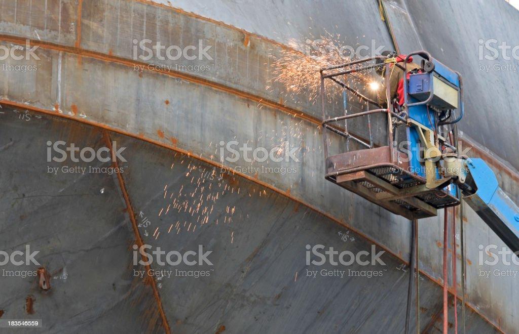 Welder with torch at shipbuilder's yard stock photo
