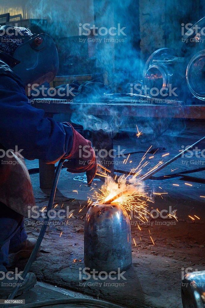 Welder worker is welding a big valve body in old factory