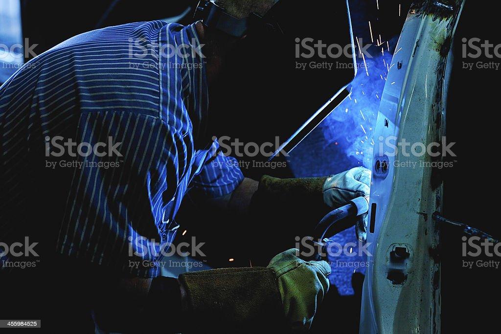 Welder working on a car door stock photo