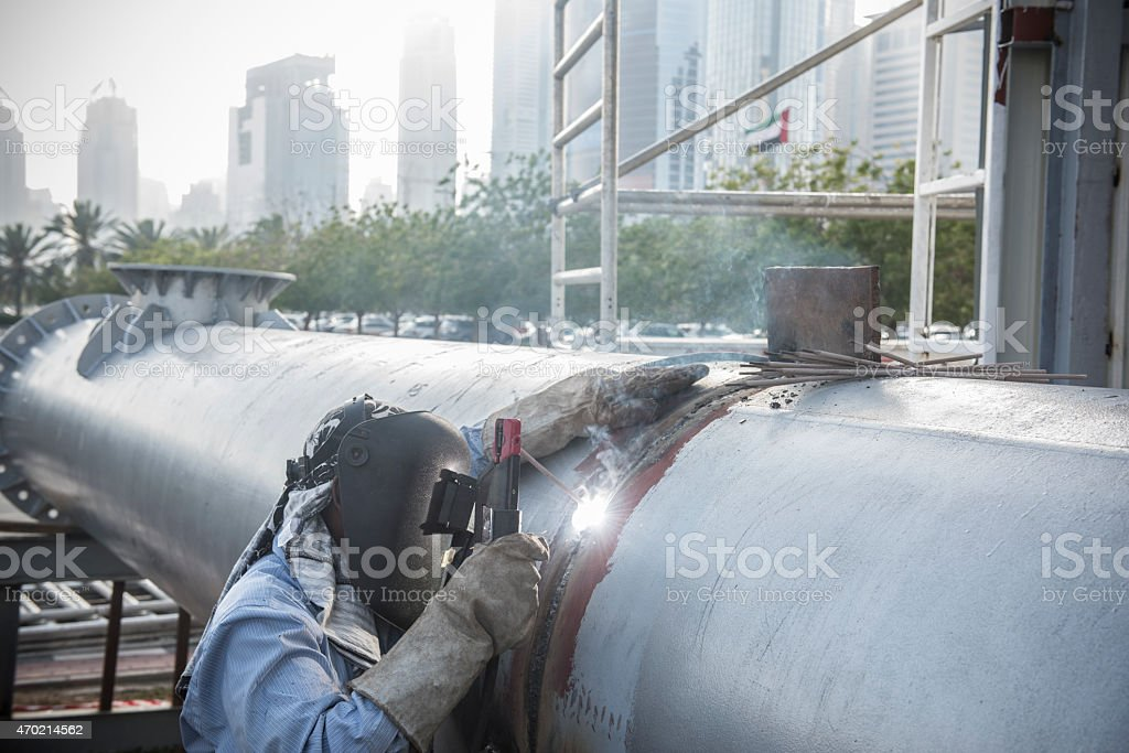 Welder working on steel pipe stock photo