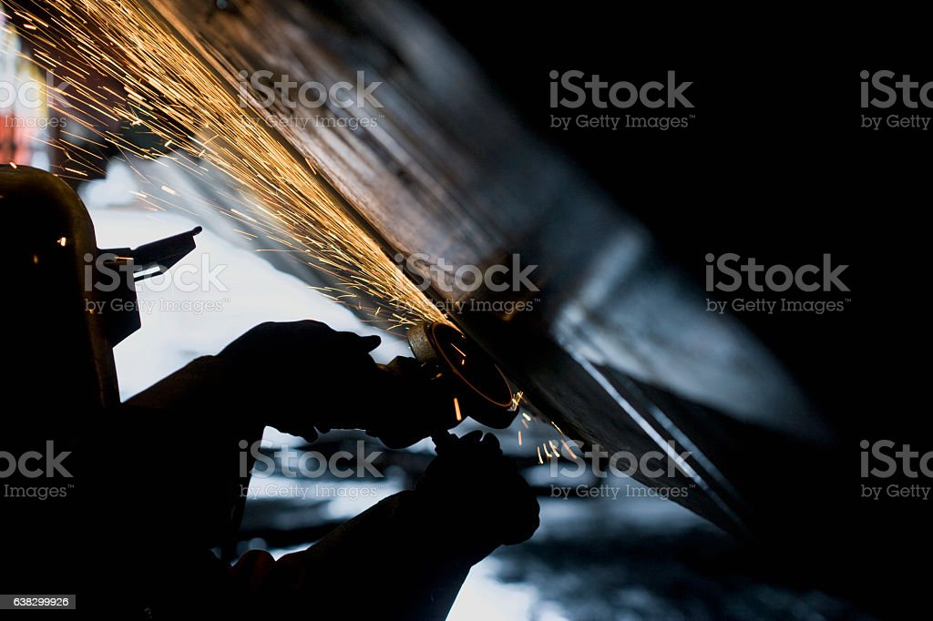 Welder working with grinder on side of a boat hull stock photo