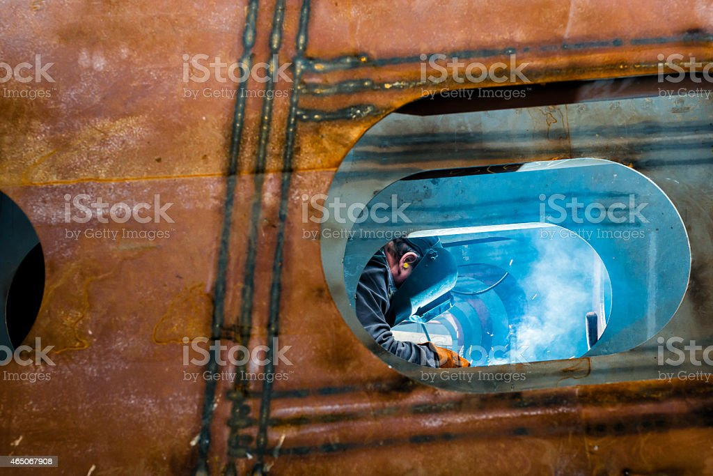 Welder working with mask on in a work shop  stock photo