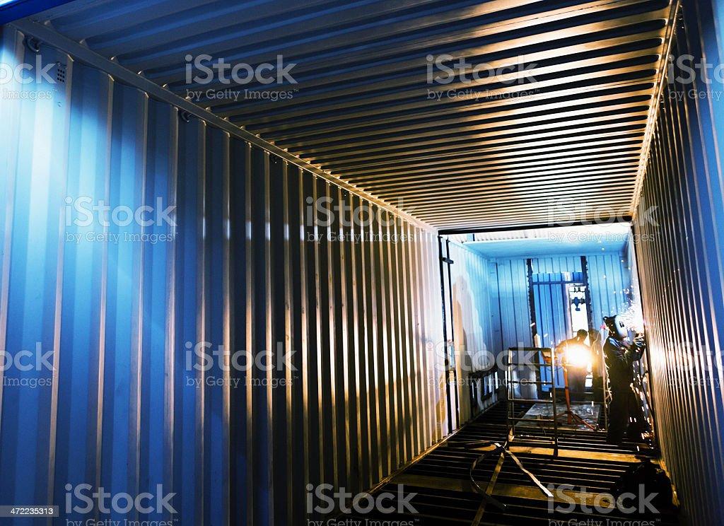 Welders working inside empty cargo container stock photo