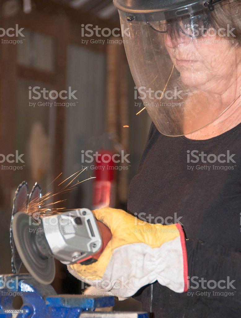 Welder-Senior woman grinding metal artpiece #1 stock photo