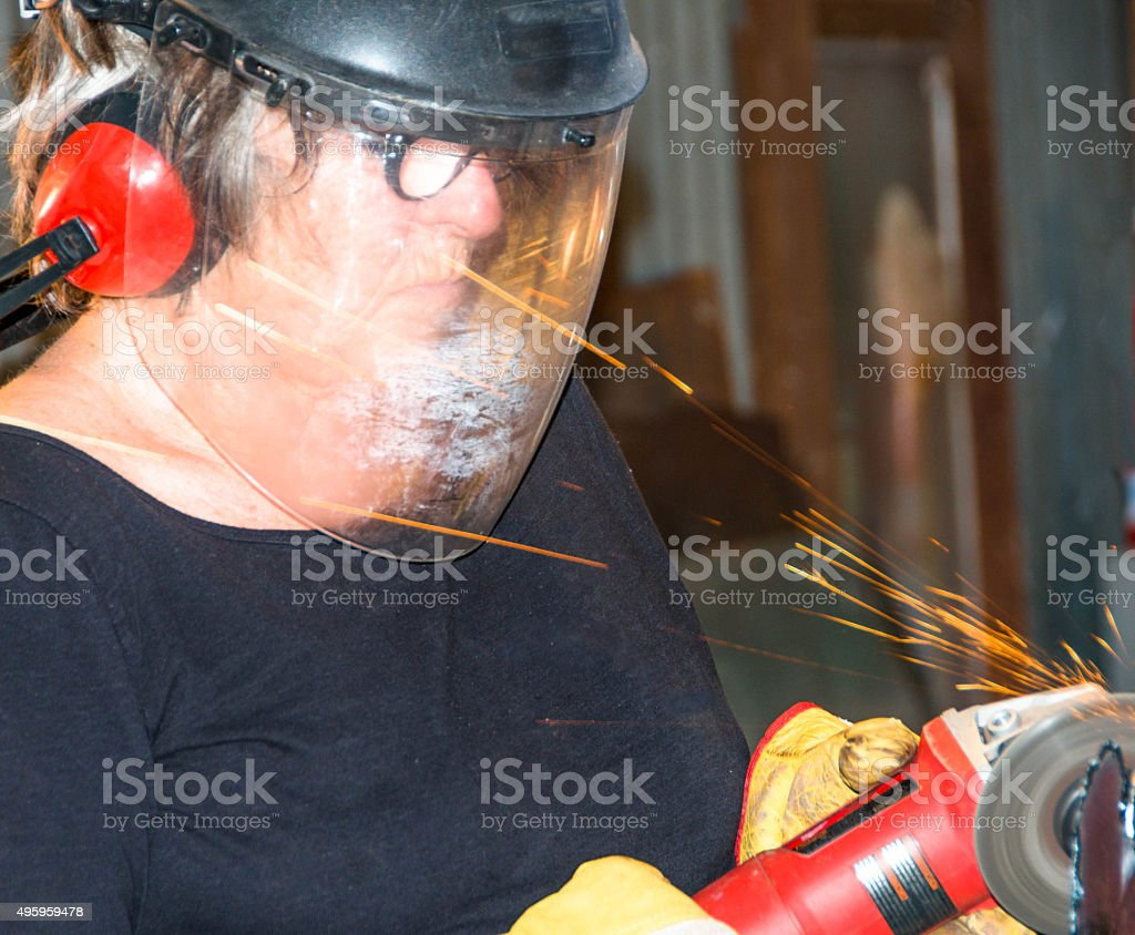 Welder-Senior woman grinding metal artpiece_6 stock photo