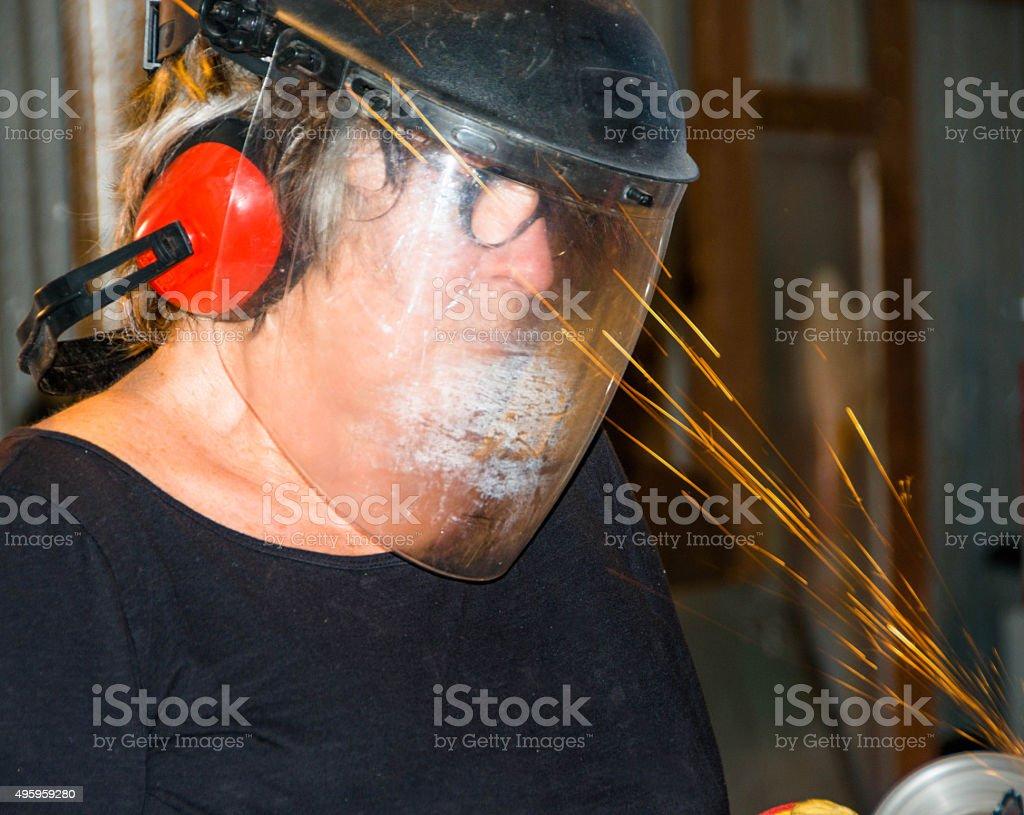 Welder-Senior woman grinding metal artpiece_7 stock photo