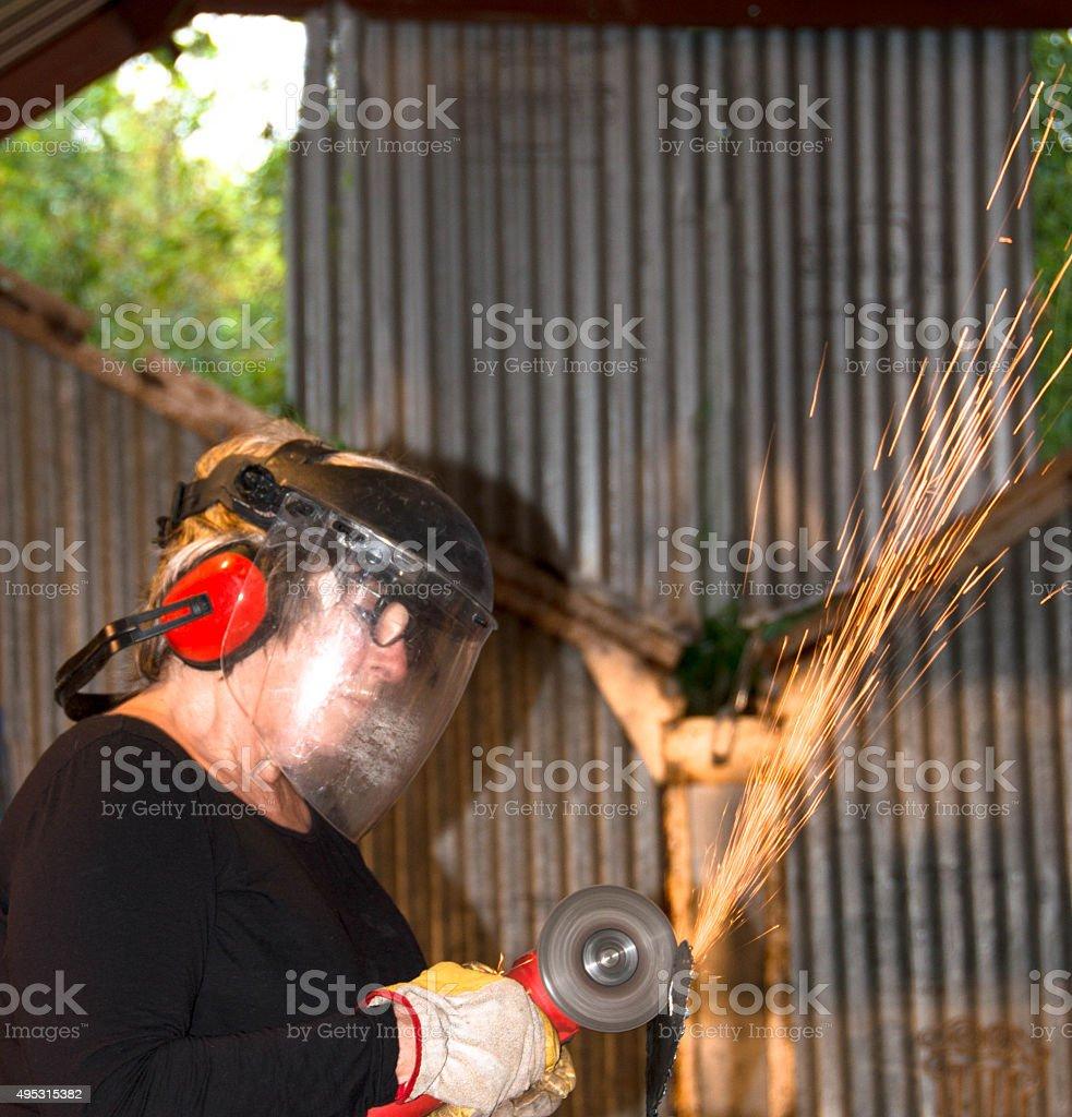 Welder-Senior woman grinding metal artpiece_8 stock photo