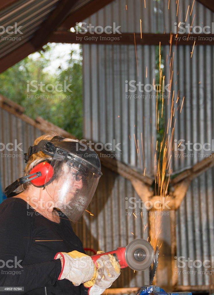 Welder-Senior woman grinding metal artpiece_9 stock photo