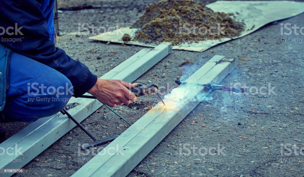 Welding of two square pipes by welding in the open air. stock photo