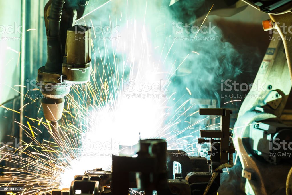 Welding robots movement in a car factory, stock photo