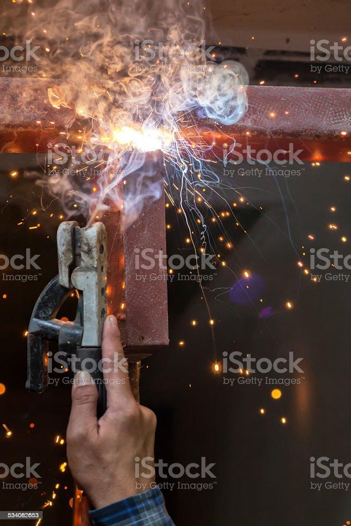 welding steel with spread spark lighting smoke stock photo