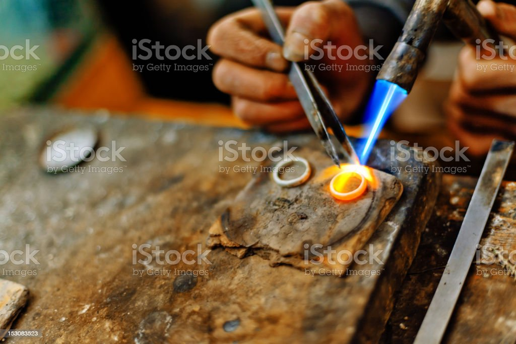 Welding torch melting the silver rings stock photo