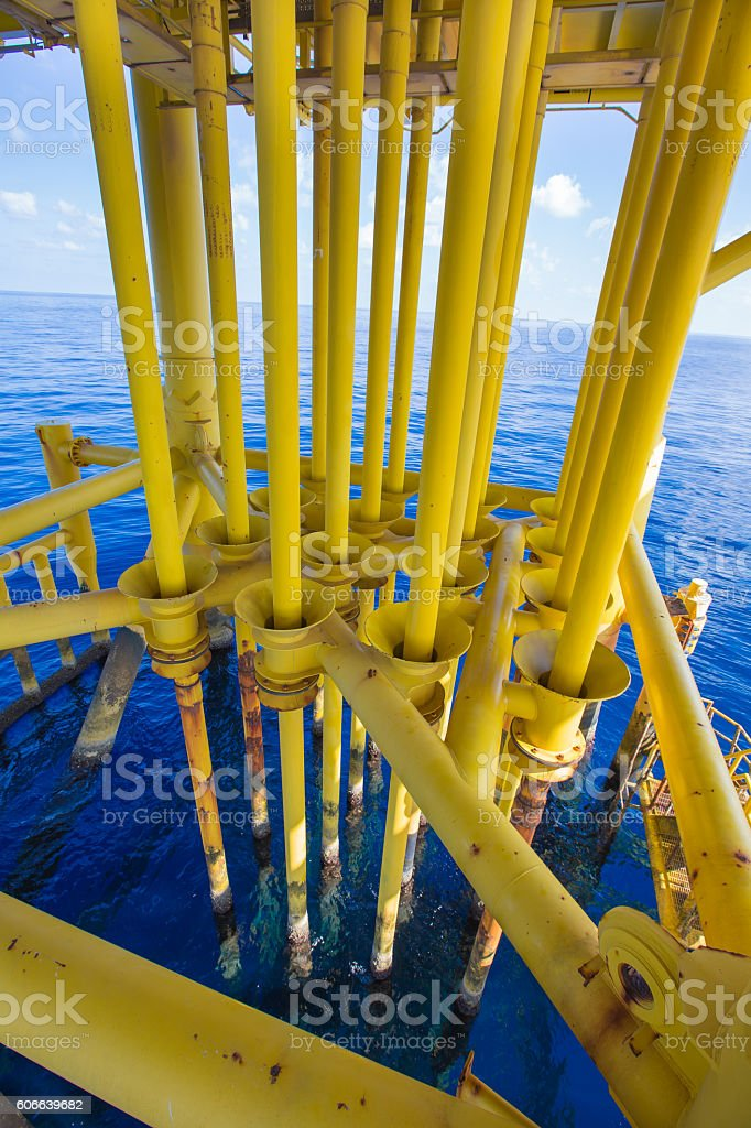 Well casing and well slot at oil and gas platform. stock photo
