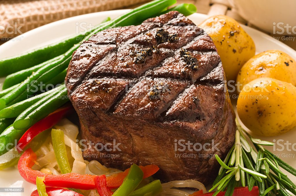 A well cooked filet of Mignon served with asparagus stock photo