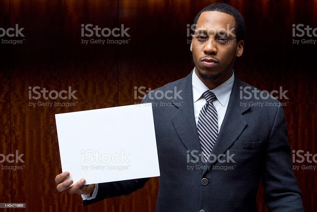 Well Dressed Businessman Holding Blank Sign Looking Tough stock photo