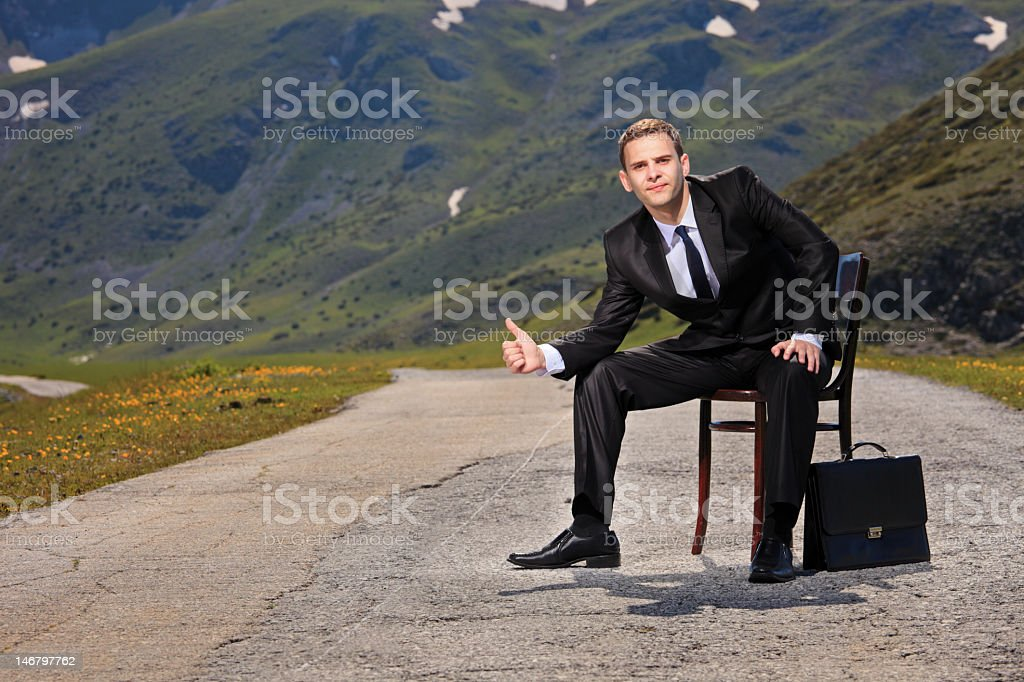 Well dressed businessman sitting while hitchhiking stock photo