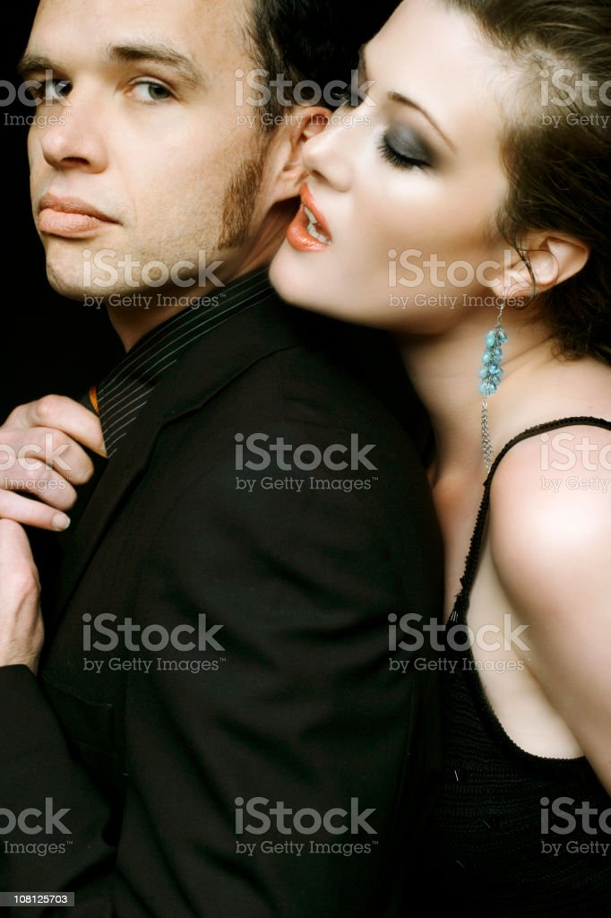 Well Dressed Couple Posing, Woman Whispering in Man's Ear stock photo