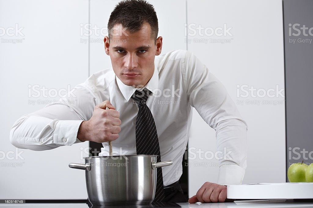 Well dressed man cooking stock photo