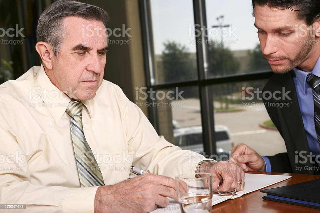 Well Dressed Man Filling Out Document with a Younger Person royalty-free stock photo