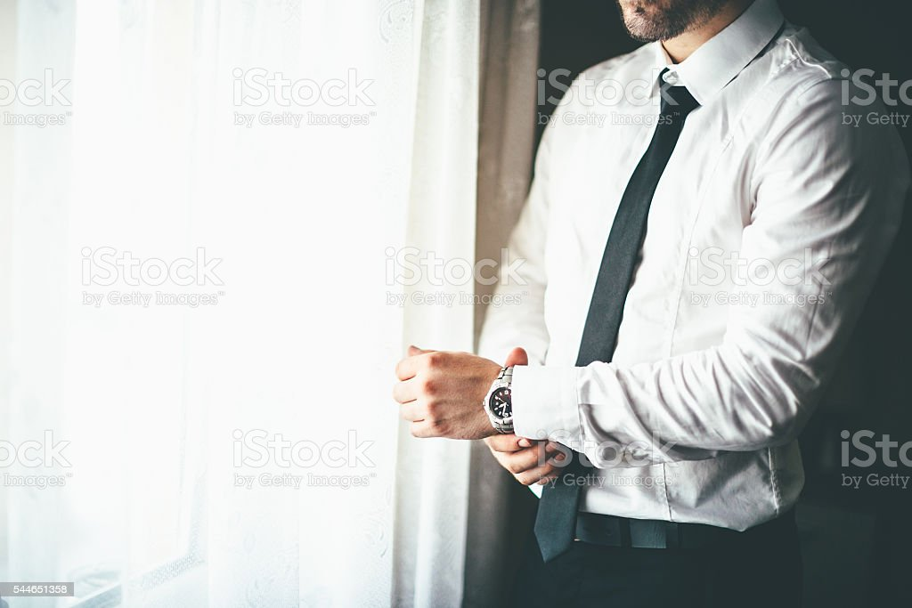 Well Dressed Man putting his wrist watch stock photo