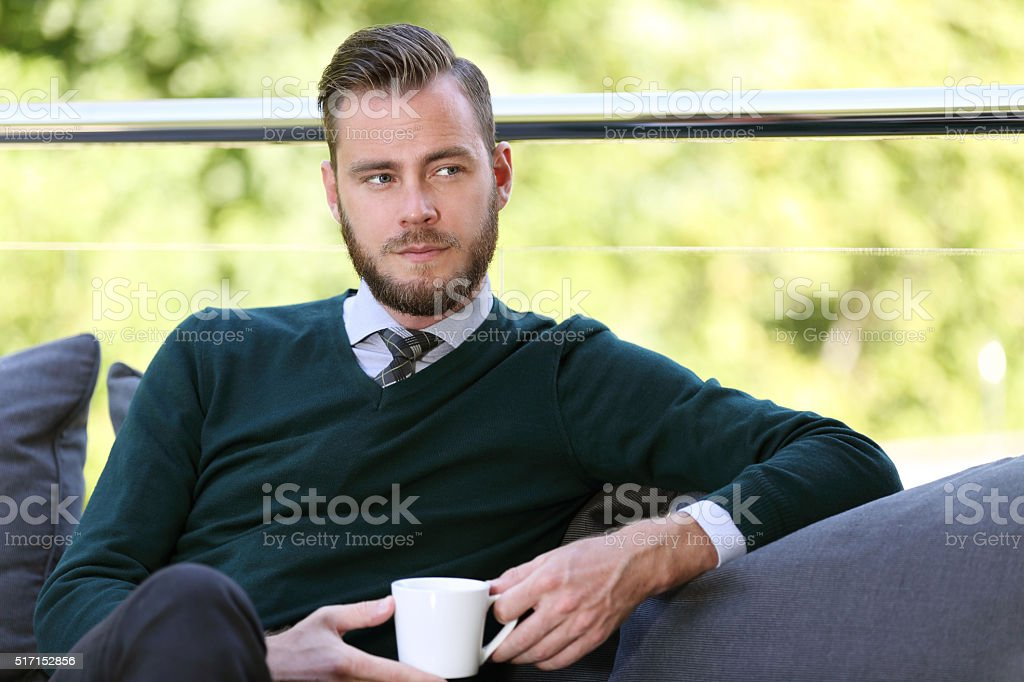 Well dressed man sitting down with mug outdoors stock photo