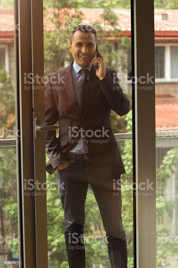 Well dressed man using smartphone at office terrace stock photo