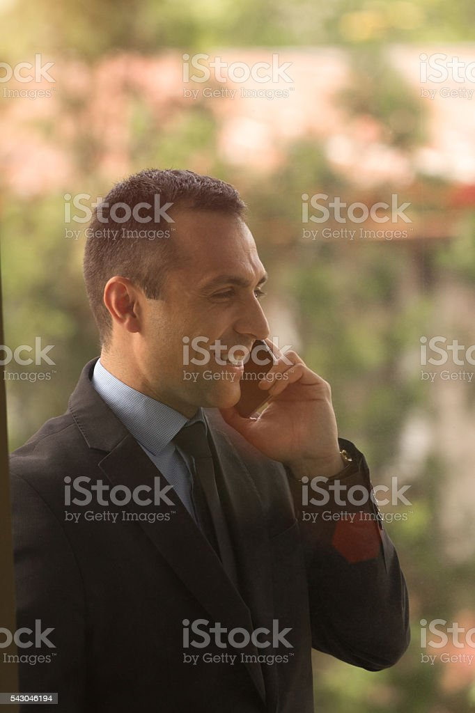 Well dressed man using smartphone, smiling stock photo