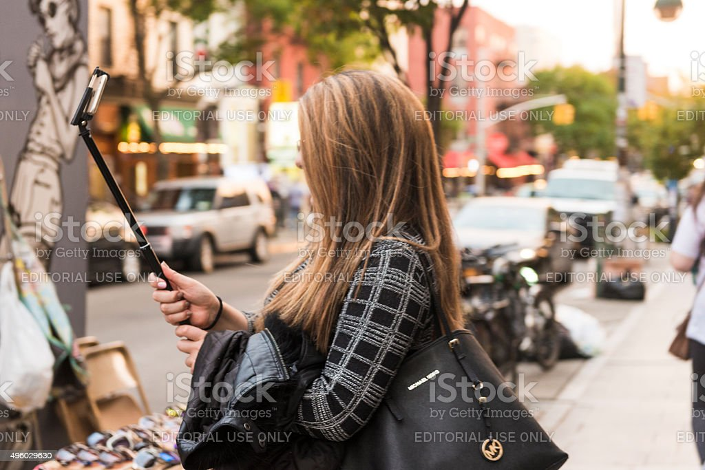 Well Dressed Woman Walks with Selfie Stick in Williamsburg NYC stock photo