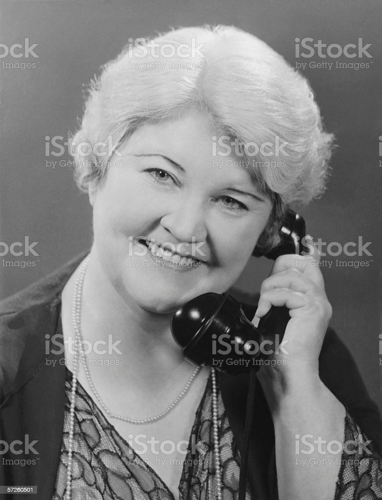 Well groomed mature woman talking on phone, (B&W), close-up, portrait stock photo