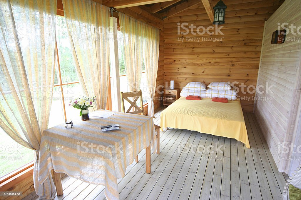 Well lit cabin bedroom with a yellow and white color scheme stock photo