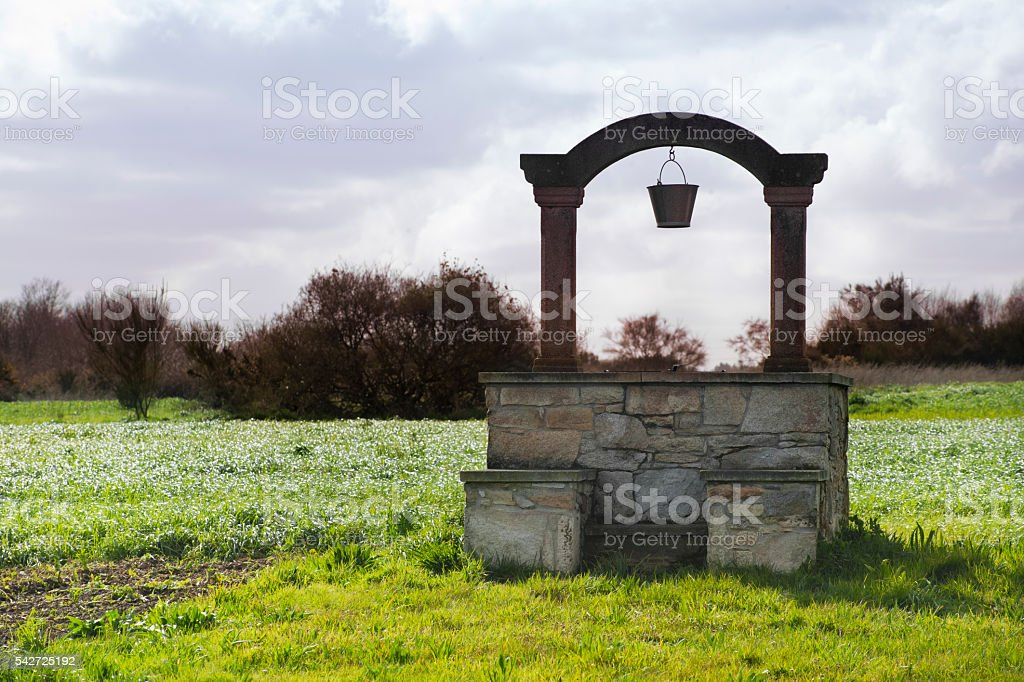 Well on a green meadow. stock photo