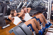 Well trained young man and woman training abdominal muscles